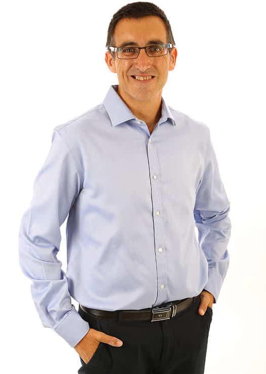 תמונה של ארז שמש מחייך ועומד לבוש חולצה מכופתרת יועץ משכנתאות פרטי