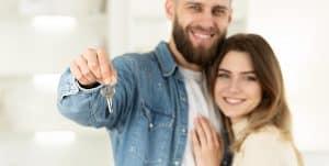 זוג עומד מחובק ומחזיק מפתח לדירה ראשונה לאחר שלקחו משכנתא לזוגות צעירים